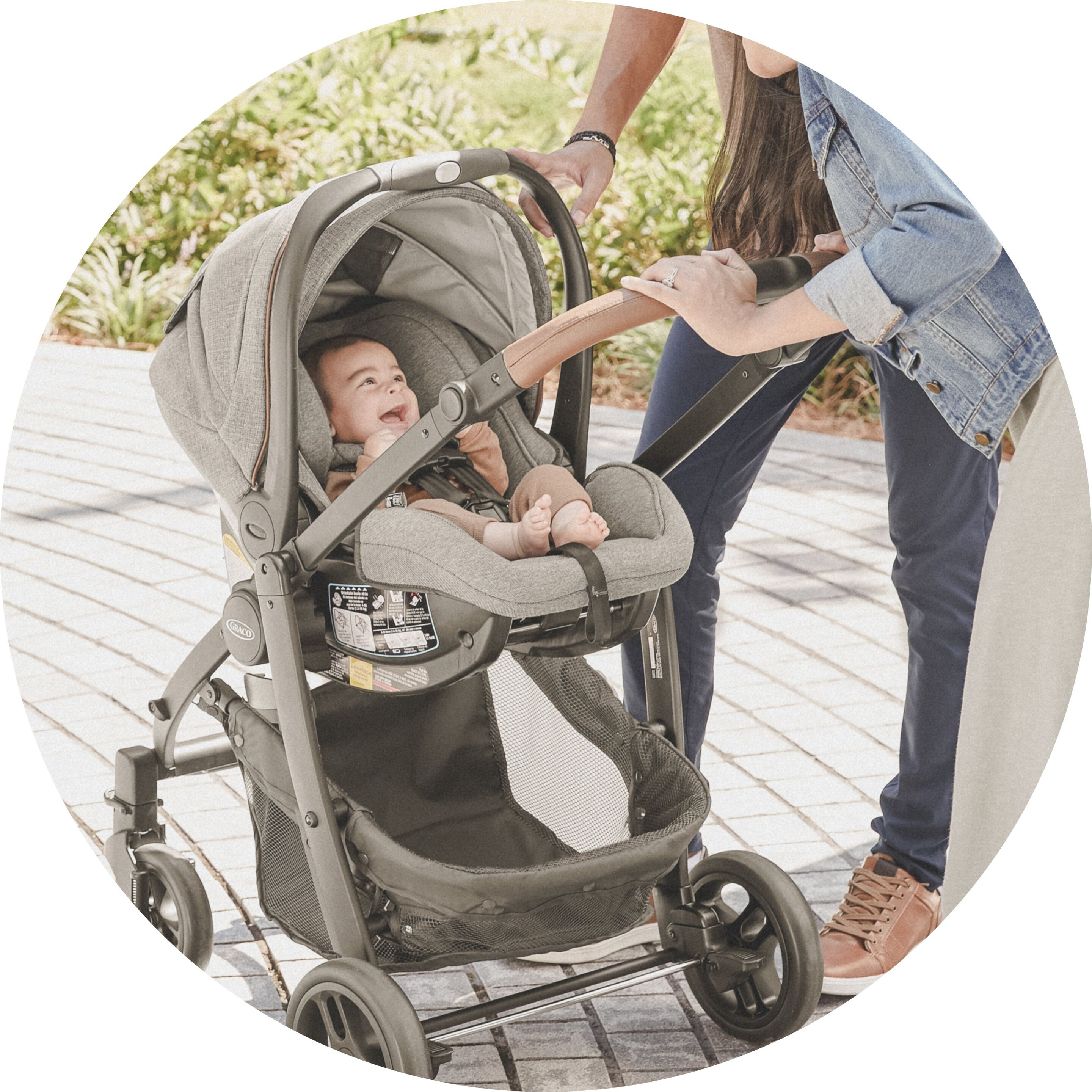parents playing with child inside premier stroller